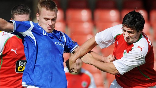 Linfield's Peter Thompson wrestles for control of the ball with  Cliftonville's Peter Hutton