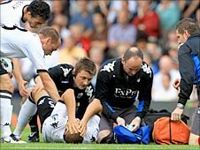Fulham players check on the stricken Bobby Zamora as he is tended to by the hosts' medical staff