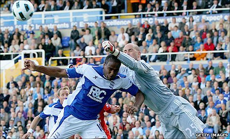 Liverpool keeper Pepe Reina (right) punches a cross before Birmingham striker Cameron Jerome can get in a header