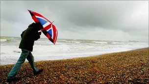 Man on beach with Union jack umbrella