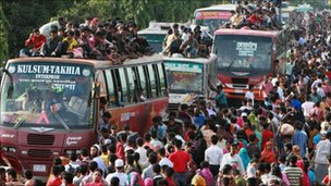 Passengers try to board buses at the Tongi bus station in Dhaka, Bangladesh