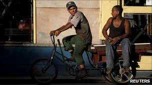 Two Cuban workers on a tricycle in Havana
