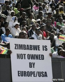 "A Zimbabwean man holds a placard among as a crowd gathers to attend commemoration of Heroes Day at the National Heroes"" acre in Harare"