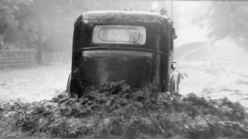 Black and white photo of car in floodwater