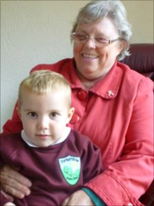 Brenda Darwood with her grandson Jake, whose older brother David, 8, wants to stay at her house so that he can experience the historic visit