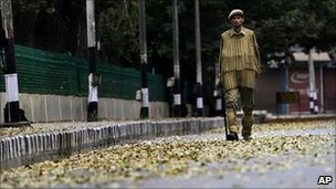 An Indian policeman patrols a deserted street during curfew in Srinagar, India on Tuesday 14 September 2010