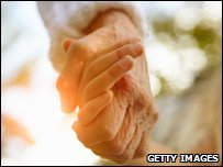 Elderly lady holding hands with  youger woman