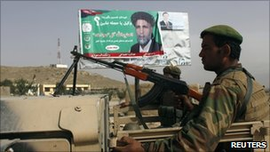 Afghan National Army soldiers in a truck in front of a poster of a candidate near Kabul on 17 September 2010
