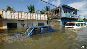 Two cars stand submerged in flood waters in Tlacotalpan, Veracruz state