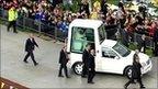 Students around Pope Benedict XVI in his Popemobile