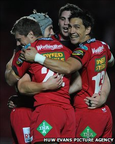 Davies (wearing head-guard) celebrates one of his three tries