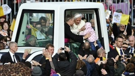 Ten-month-old Ronke Ijanson is handed to the Pope
