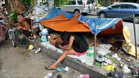 A homeless living under a tarpaulin on a flower bed in the middle of Manila on 2 September, 2010