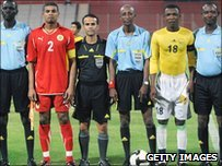 Bahrain captain Mohammed Hussein (red shirt) lines up ahead of the match