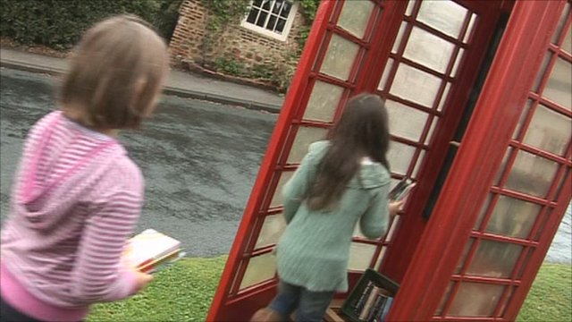 Children at phone box 'library'