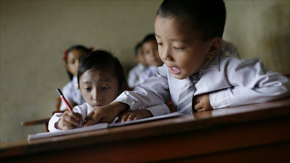Khagendra Thapa Magar writes in class, helped by a school   friend (Photo by Tom van Cakenberghe)