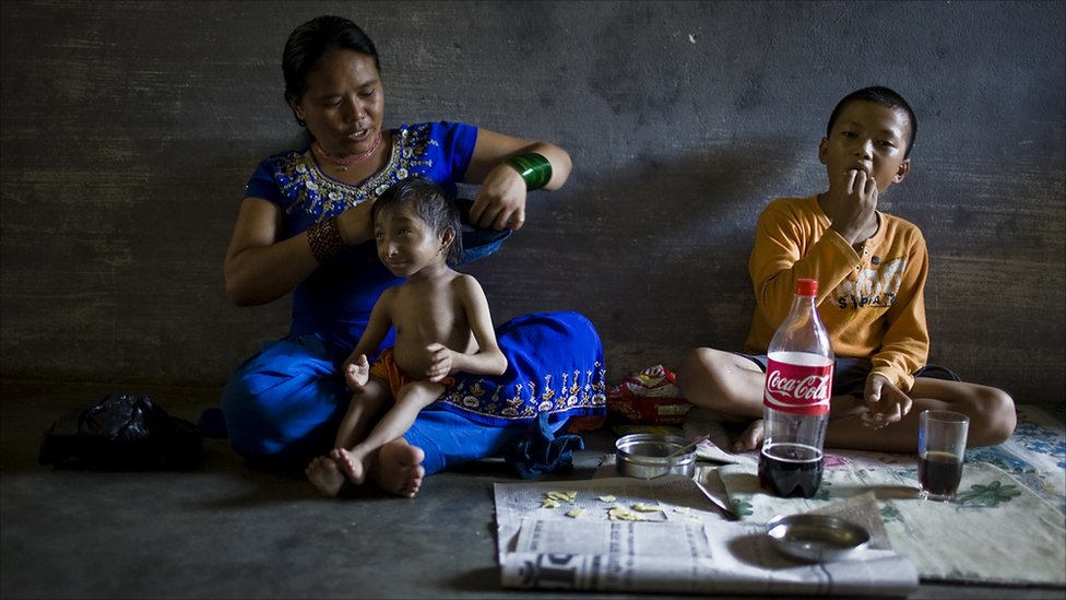 Dhana Maya helps her son, Khagendra Thapa Magar, change out of his clothes after school (Photo by Tom van Cakenberghe)