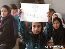 A female student holds up a peace sign as she waits for Kofi Annan to visit her school in 2002