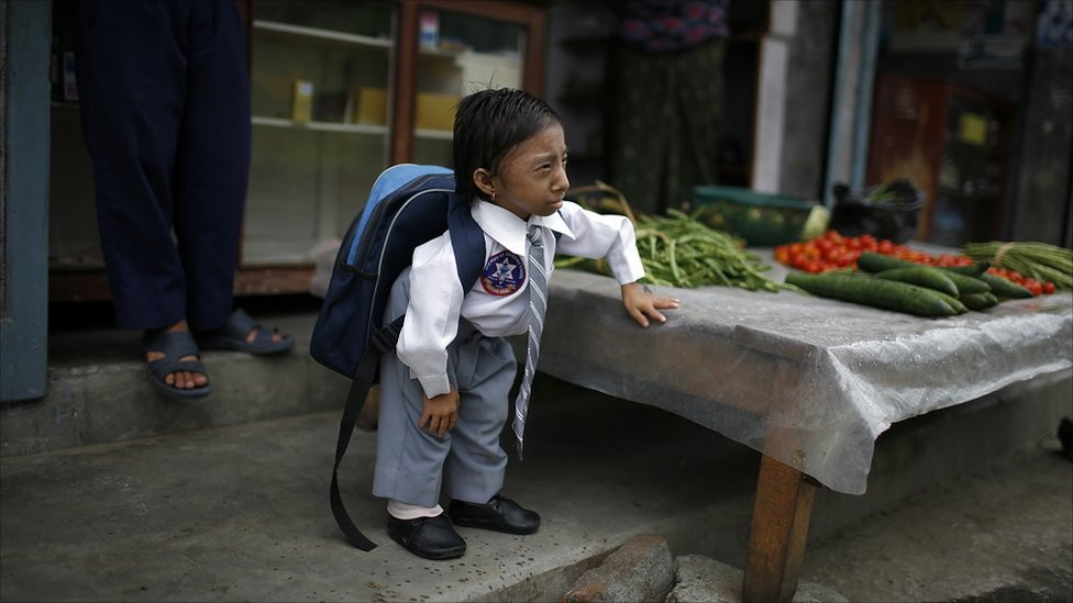 Khagendra Thapa Magar stands in his school uniform in preparation for his school-day (Photo by Tom van Cakenberghe)
