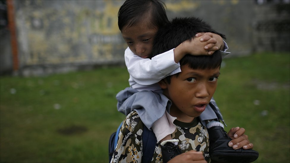 Khagendra Thapa Magar is carried to school on his brother's back (Photo by Tom van Cakenberghe)