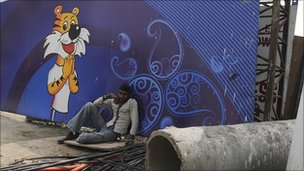 A man rests in front of a Games advertising hoarding in Delhi on Thursday