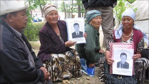 Kyrgyz mothers hold photos of missing relatives