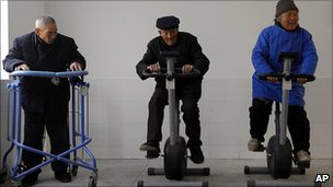 Elderly Chinese people on exercise machines at a home for the elderly in Jiangsu province