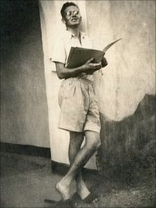 Archive photo of John Smith in shorts, with a book