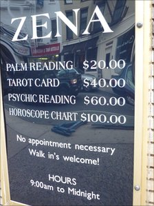 A sign listing the prices for fortune teller services