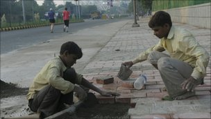 Indian workers finish a pavement near Nehru Stadium in New Delhi on 25 September
