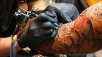 Tattooist sketching design on man's arm