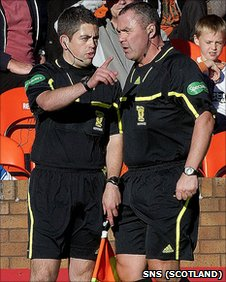 Referee Brian Winter (right) consults his linesman  at Tannadice