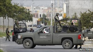 Soldiers stand guard during a drugs raid in Monterrey in August 2010