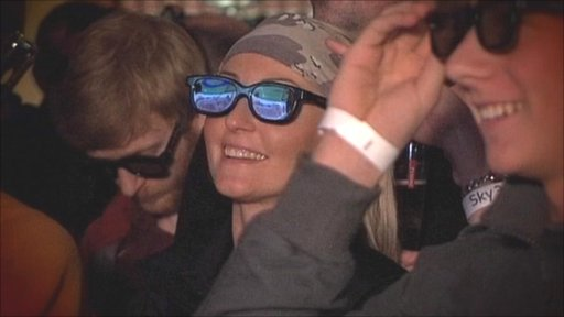 People in a pub watching 3D TV