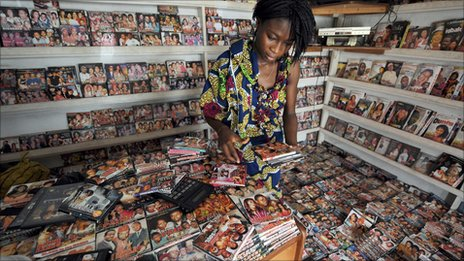 A sales person sorts through DVDs in a shop at the Nigerian film market in Lagos