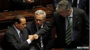 Silvio Berlusconi (left) is congratulated by allies Umberto Bossi (right) and Giulio Tremonti (centre)