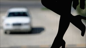 Silhouette of prostitute's legs with a car approaching