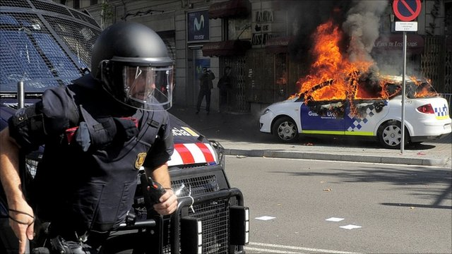 A riot police runs as a patrol police car burns during riots in Barcelona