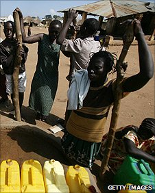 (2005 photo) Internally displaced people collect water at a pump in a camp
