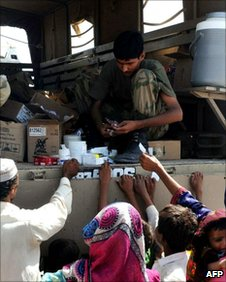 Pakistani soldier handing out flood supplies