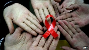 Chinese students show a handmade red AIDS ribbon.  Hanshan, Anhui province, China