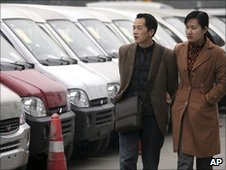 Chinese couple looking at minivans