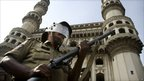 An Indian policeman stands guard in front of the landmark Charminar mosque in Hyderabad
