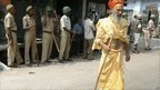 Indian holy man walks past soldiers in Ayodhya