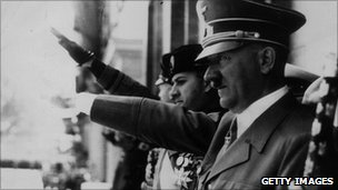 Circa 1944: Adolf Hitler (1889 - 1945) gives the fascist salute at a parade during WWII. Visible on the balcony with him are Galeazzo Ciano and Italian Benito Mussolini (far left).