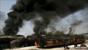Police collect bullets shells next to burning oil tankers in Shikarpur, Sindh province, on 1 October 2010