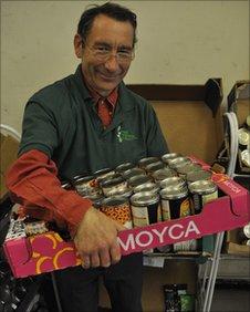 Foodbank volunteer Peter Moss with tinned food