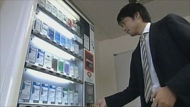A man buys cigarettes from a vending machine