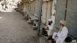 Tribesmen sit along a closed market in Miranshah, the capital of North Waziristan