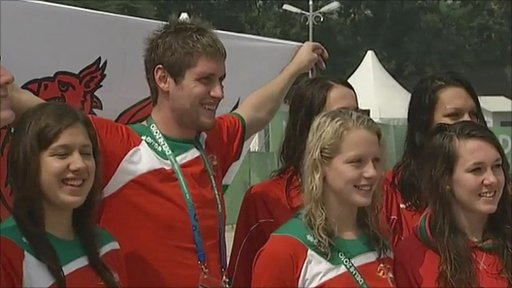 David Davies holds the Welsh flag amongst his swimming team-mates